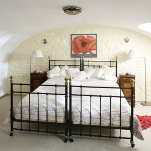 Kute łóżko doskonale prezentuje się na tle jasnej, ceglanej ściany. Klasyczne stoliki nocne, komoda oraz oświetlenie dodają wnętrzu uroku. Fot. Archiwum Dobrze Mieszkaj.