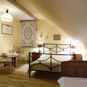 W jasnej, przytulnej sypialni urządzonej na poddaszu zdecydowano się wyłącznie na klasyczne meble. Dekoracyjna szafa, stoliki nocne w połączeniu z dekoracyjną formą oświetlenia tworzy klimatyczne wnętrze. Fot. Archiwum Dobrze Mieszkaj.
