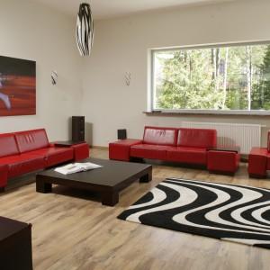 W dużym wnętrzu można pozwolić sobie na odrobinę ekstrawagancji. Modernistyczne, czerwone sofy i fotel ustawiono wzdłuż ścian. Centralne miejsce zajmuje niski stolik i dywan inspirowany umaszczeniem zebry. Projekt: Maciej Matłowski. Fot. Bartosz Jarosz.