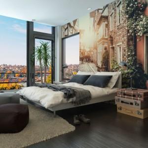 Fototapeta przedstawiająca widok na uroczą uliczkę została umieszczona na całej szerokości ściany za łóżkiem. Przestrzenna fototapeta optycznie powiększa przestrzeń. Fot. Minka.