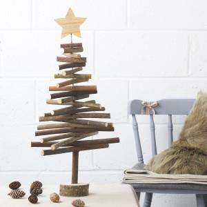 Trochę minimalistyczne, bardzo ekologiczne i oryginalne drzewko świąteczne wykonane z grubych patyków i solidnego drutu. Rolę stojaka pełni pień drzewa. Fot. The Contemporary Home.