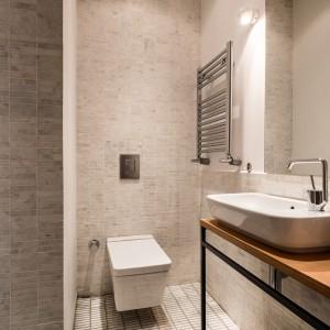 Dominujące w drugiej łazience szarości, nadają jej stonowany, elegancki wyraz. Bezramowe lustro na ścianie idealnie komponuje się z geometrycznym kształtem wc. Projekt: Atelye70. Fot. Emrah Aydemir.