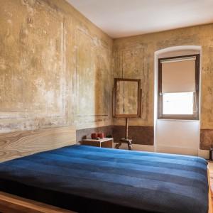 Na ścianach w mieszkaniu pozostawiono zabytkowe freski, które odrestaurowano. Nadają one wnętrzu jednocześnie surowy wygląd (wrażenie niewykończonej ściany), jak i ocieplają je delikatnie mieszanką brązu i beżu. Kolorystyka pięknie komponuje się z drewnianą podłogą. Projekt: Atelye70. Fot. Emrah Aydemir.