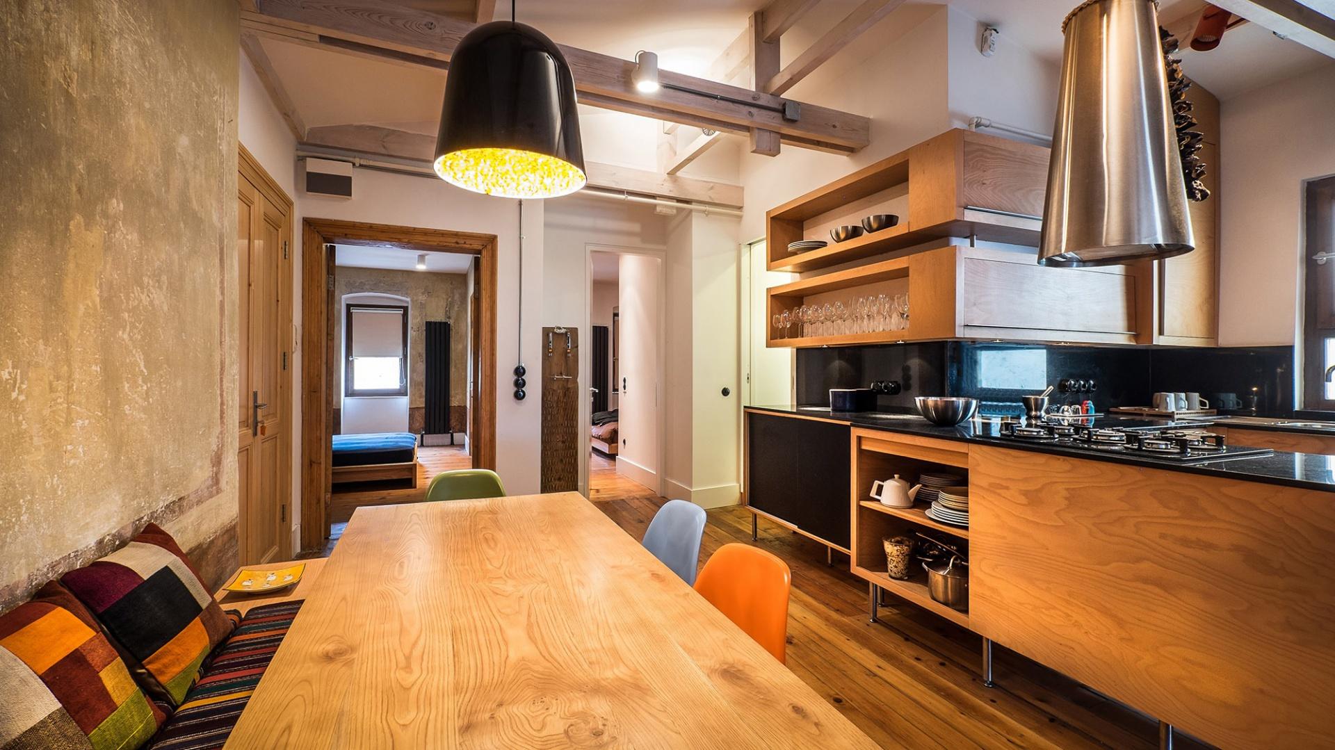 Jadalnię od kuchni umownie oddziela półwysep kuchenny. Drewniany stół jadalniany pięknie komponuje się z drewnianymi meblami kuchennymi. Projekt: Atelye70. Fot. Emrah Aydemir.