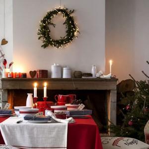 Na czerwonym obrusie poprowadzono biały bieżnik. Kontynuację kombinacji tych samych barw znajdziemy również w postaci zastawy stołowej i towarzyszących jej dwóch czerwonych świeczników z białymi świecami. Fot. H&M Home.