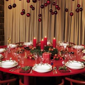 Czerwień ponad wszystko! Stół, dekoracyjne bombki nad stołem, nawet świeczki i krzesła. W tej aranżacji dominuje ognista, gorąca czerwień. Tak mocną kolorystkę warto stonować delikatniejszymi elementami. Tutaj przełamana została elegancką zastawą w tradycyjnej bieli i subtelnym szkłem. Krawędzie talerzy zdobi świąteczny motyw.  Fot. Royal Copenhagen.