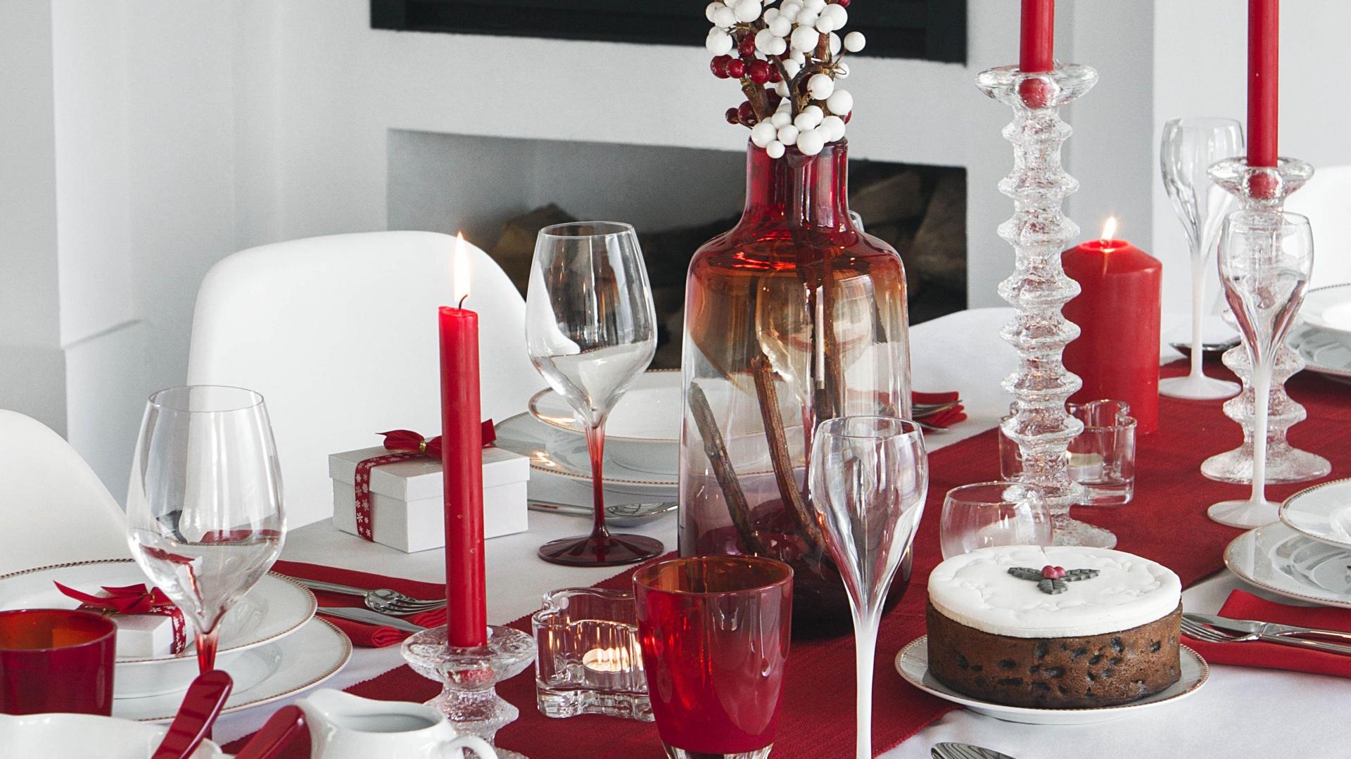 Elegancja i przytulny charakter w jednym. Duet czerwieni i bieli pięknie prezentuje się w formie dekoracji stołu. Blat udekorowany białym obrusem został dodatkowo przykryty czerwonym bieżnikiem, ułożonym wzdłuż stołu. Z białą porcelaną pięknie współgrają czerwone świece i serwetki. Czerwono-białe są również dekoracyjne szklane bazie, będące centrum całej aranżacji. Fot. Amara Home.