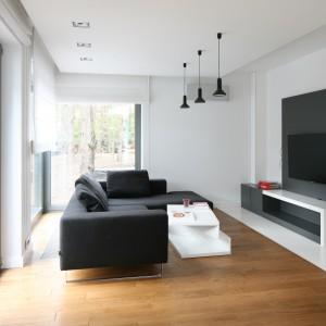 Salon jest nowoczesny, minimalistyczny, oszczędny w ozdobne detale, ale też bardzo elegancki. Stanowi przedłużenie tego, co widać na zewnątrz. Stąd we wnętrzu pojawia się ciepłe, jasne drewno dębu o ładnej, delikatnej fakturze, które równoważy chłodny w odbiorze bazalt i trawertyn. Całość doskonale prezentuje się na tle stonowanej bieli. Projekt: Katarzyna Kiełek, Agnieszka Komorowska-Różycka. Fot. Bartosz Jarosz.