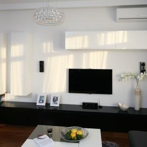 Białe ściany salonu pozwoliły wyeksponować wszystkie dekoracje wnętrza. Podkreśliły też niezwykły urok ciemnej drewnianej podłogi. Projekt: Anna Maria Sokołowska. Fot. Bartosz Jarosz.