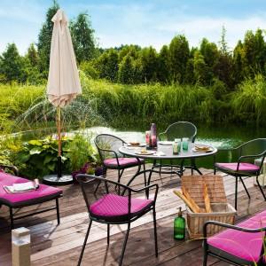 Przestronny taras położony w pobliżu małego zbiornika wodnego stwarza w ogrodzie przyjemne miejsce do odpoczynku. Fot. Castorama.