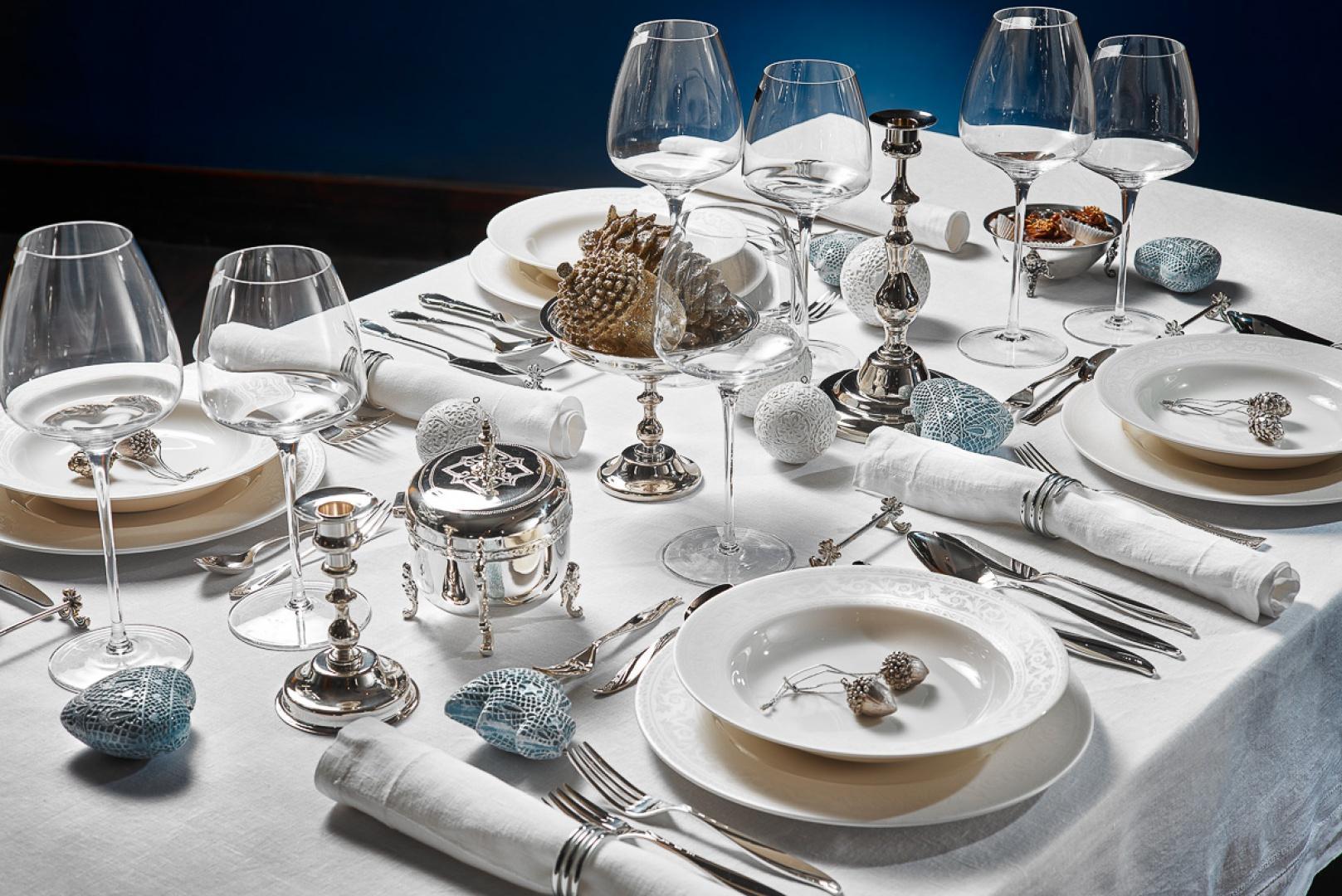 Piękny świąteczny stół, na którym pierwsze skrzypce gra biel, zamknięta w srebrzyste akcenty. Biały obrus, porcelana i serwetki pięknie harmonizują ze srebrnymi świecznikami i dekoracyjnymi bombkami w kolorze srebrnoniebieskim i białym. Fot. Herfa Fabryka Platerów.