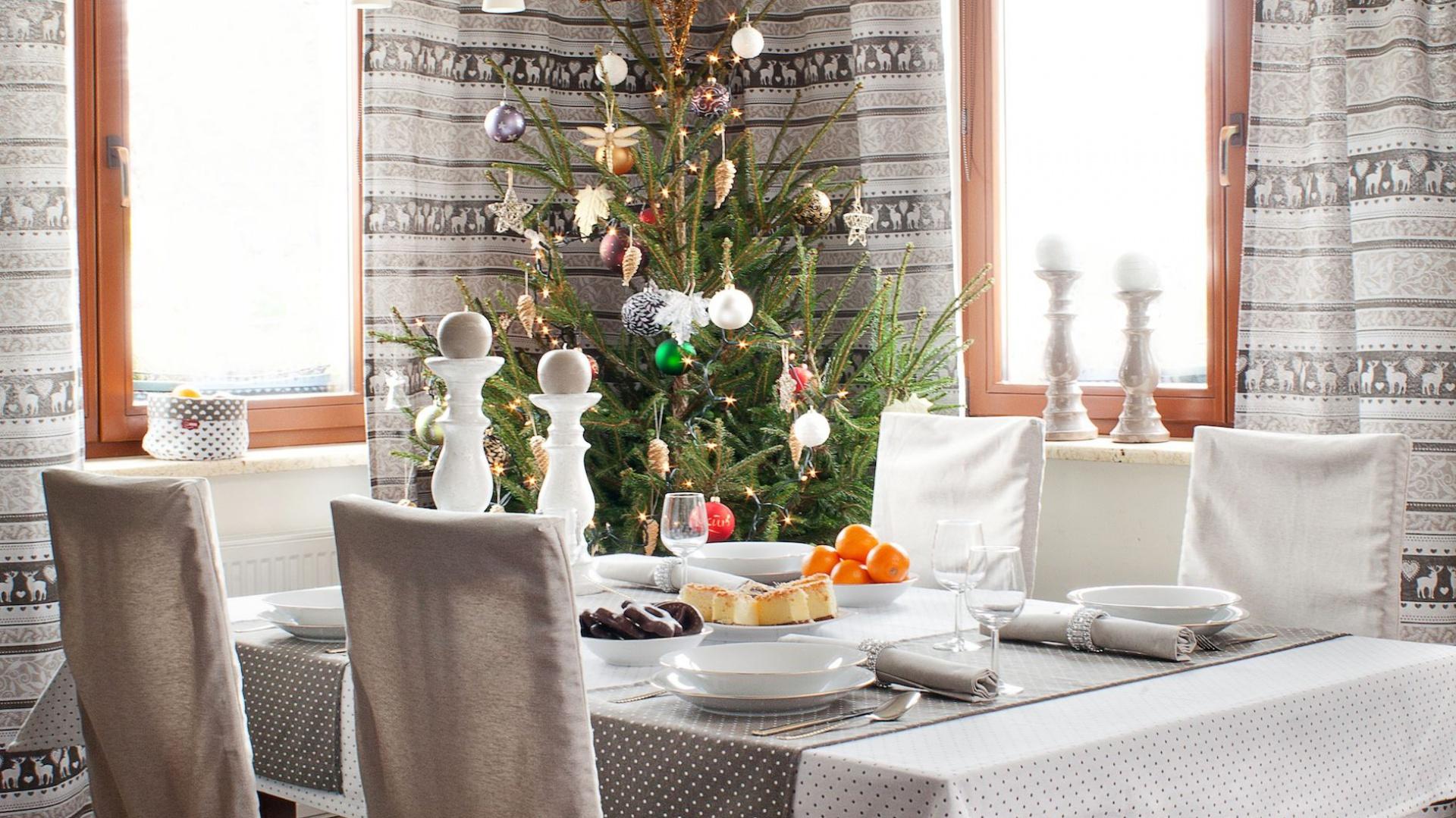 W tej aranżacji króluje śnieżnobiała biel. Biała jest porcelana, narzuty na krzesła, a nawet świeczniki! Dominującą biel przełamują dwa bieżniki w delikatnej szarości. Fot. Dekoria.