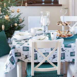Aranżacja stołu, w której króluje chłodny turkus i biel. Obrus ze świątecznym motywem reniferków pięknie komponuje się z białą porcelaną. Fot. Dekoria.