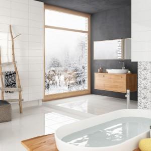 Płytki bazowe białe oraz białe z czarnym graficznym dekorem z kolekcji Penne marki Opoczno stanowią tło przytulnej aranżacji. Łazienkę ociepla drewno w postaci mebli i dodatków. Fot. Opoczno.