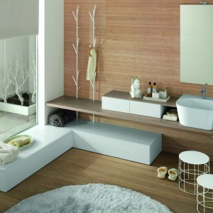 Seria kompletnego wyposażenia łazienki Canestro firmy Novello to białe meble, ceramika i dodatki o ciekawej, stylowe formie. Wykończenie podłogi i ścian w drewnie dodaje przytulnego charakteru. Fot. Novello.