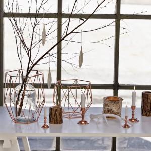 Inspiracje naturą będą odmianą od wesołych bożonarodzeniowych dekoracji. Drewniane świeczniki pięknie kontrastują z metalowymi przestrzennymi osłonami na wazony. Fot. Hübsch.