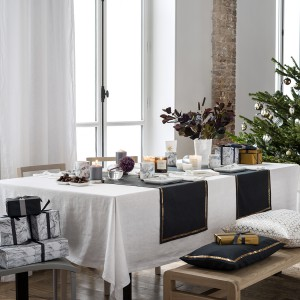 Granatowe bieżniki ze złotymi lamówkami świetnie prezentują się na białym obrusie. Elegancka aranżacja bez zbędnego przepychu.  Fot. H&M.