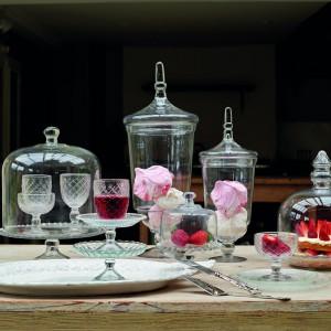Eleganckie szklane patery z pokrywami i kryształowe kieliszki na smakowite trunki. Do uzupełnienia aranżacji brakuje tylko sylwestrowego szampana, który przecież znakomicie pasuje do truskawek. Fot. Parlane.