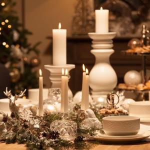 Zimowa biel inspiruje do tworzenia wytwornych aranżacji. Świeczniki i figurki jelenia oraz ptaszków nadają kompozycji przytulności. Przy takim stole każde przyjęcie będzie udane. Fot. Almi Decor.