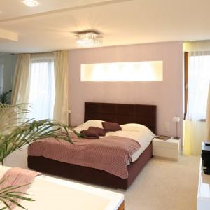 W tej nowoczesnej sypialni właściciele mogą korzystać z oświetlenia sufitowego w postaci pięknego żyrandola, jak również z lampek nocnych. Kolejnym źródłem światła jest podświetlona wnęka nad łóżkiem. Projjekt: Katarzyna Mikulska-Sękalska. Fot. Bartosz Jarosz.