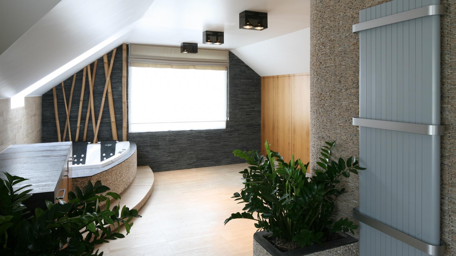 Duża, dwuosobowa wanna z hydromasażem  stanowi centrum strefy relaksu. Obudowa została wykończona kamienną mozaiką, a łodygi bambusów w roli dekoracji podkreślają naturalny styl aranżacji. Projekt: Karolina Łuczyńska. Fot. Bartosz Jarosz.