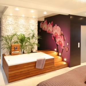 Ta łazienka została urządzona w sypialni. Połączona przestrzeń pełni funkcje strefy relaksu, taki jest też jej charakter, co podkreślają rośliny, nastrojowe oświetlenie i wanna w obudowie z drewna egzotycznego. Projekt: Katarzyna Mikulska-Sękalska. Fot. Bartosz Jarosz.