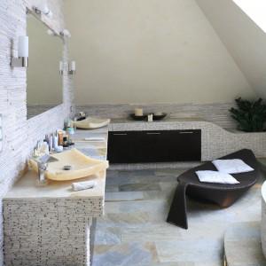 Aranżacja oddająca klimat rodem z egzotycznej wyspy to pewny sposób na urządzenia łazienki jako miejsca relaksu. Naturalne materiały zostały wykorzystane na okładziny, ale też pięknie wyglądają kamienne umywalki. Projekt: Karolina Łuczyńska. Fot. Bartosz Jarosz.