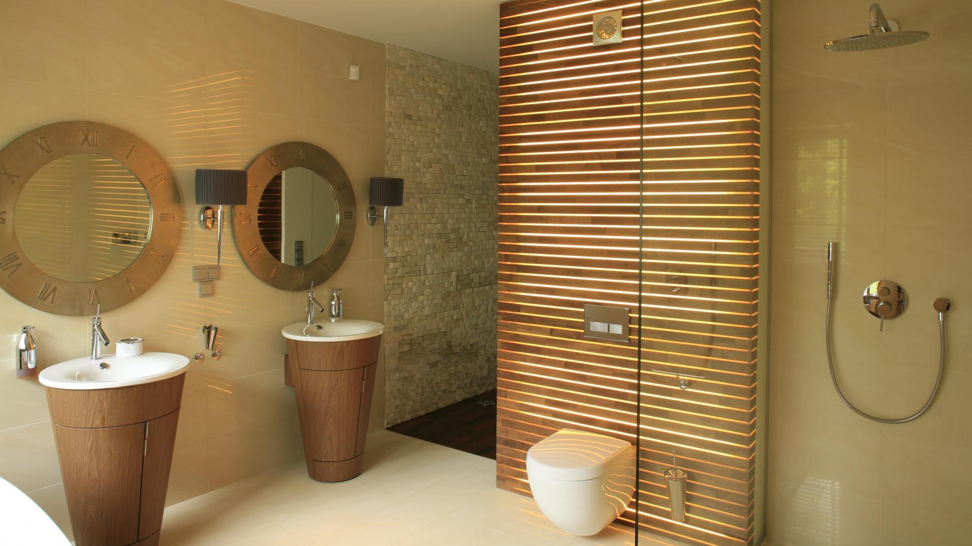 W przestronnym salonie kąpielowym można korzystać z natrysku w kabinie typu walk-in, która zapewnia maksimum komfortu. Także aranżacja z wykorzystaniem naturalnych materiałów sprzyja relaksowi. Projekt: Natalia Rychtelska, Beata Czechowicz. Bartosz Jarosz.