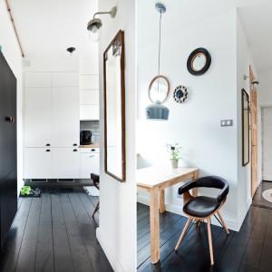 Kolorystyka dominująca w mieszkaniu nawiązuje do stylu skandynawskiego. Subtelny zestaw bieli i ciepłego drewna uzyskał mocniejszy akcent w postaci czerni w formie podłogi, szafy w korytarzu i dodatków. Projekt: Magdalena Ilmer, Boho Studio. Fot. Boho Studio.