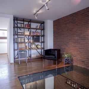Część podłogi trzeciej kondygnacji mieszkania została usunięta i zastąpiona przeszkleniami. Zabieg ten dodał wnętrzu lekkości oraz pozwolił na swobodny przepływ światła pomiędzy piętrami. Projekt: B² Architecture. Fot. Michal Šeba.