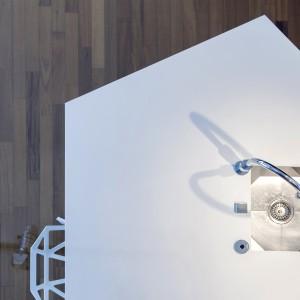 Półwysep urzeka nietuzinkowym, geometrycznym kształtem. Ostre kąty i niebanalna forma są kontynuowane również w stylistyce zlewozmywaka, który  estetycznie schowano w blacie. Projekt: B² Architecture. Fot. Michal Šeba.