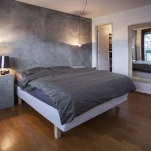 Industrialny charakter w master bedroom buduje szara ściana, wykończona tynkiem imitującym beton oraz oświetlenie w formie odsłoniętych żarówek wyeksponowanych na czerwonych kablach. Z sypialni można bezpośrednio przejść do garderoby i łazienki. Projekt: B² Architecture. Fot. Michal Šeba.