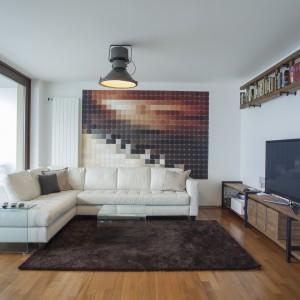 W salonie przytulny klimat spotyka się z industrialnym chłodem. Tradycyjny narożnik wypoczynkowy i miękki dywan nadają wnętrzu domowy charakter, podczas gdy surowe drewno i techniczne oświetlenie nawiązują do stylistyki loftowej. Na ścianie za narożnikiem znajduje się mozaika przedstawiająca wypikselowane pianino - nawiązując tym samym do profesji właścicieli, ale wpisując się w nowoczesną stylistykę. Projekt: B² Architecture. Fot. Michal Šeba.