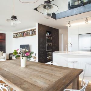 Przestrzeń dzienną urządzono na otwartym planie. Nowoczesna kuchnia z półwyspem, jadalnia i salon stanowią spójną kolorystycznie całość. Projekt: B² Architecture. Fot. Michal Šeba.