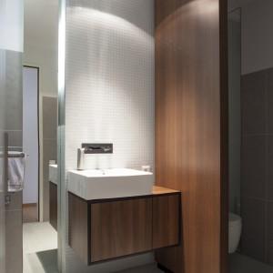 W łazience królują kubistyczne formy i barwy konsekwentnie nawiązujące do kolorystyki całego mieszkania. Nablatowa, prostokątna umywalka pięknie wyeksponowana została przez czekoladowy kolor drewna. Projekt: B² Architecture. Fot. Michal Šeba.