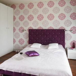 Wzorzysta tapeta stanowi doskonałe tło dla łóżka z wysokim, tapicerowanym zagłówkiem w pięknym, fioletowym kolorze. Zagłówek zdobią także delikatne kryształy. Projekt: Beata Ignasiak-Wasik. Fot. Bartosz Jarosz.