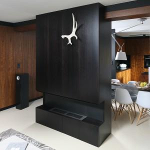 Chłodną, minimalistyczną kolorystykę wnętrza przełamuje drewno w wybarwieniu orzecha amerykańskiego. To nim udekorowano jedną ze ścian salonu. Jego ciepło podkreśla zamontowany tu biokominek.  Projekt: Kasia Dudko, Michał Dudko. Fot. Bartosz Jarosz.