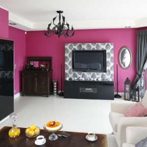 W kobiecym salonie duży telewizor doskonale prezentuje się na tle ścian w kolorze fuksji. Projekt: Beata Ignasiak-Wasik. Fot. Bartosz Jarosz.
