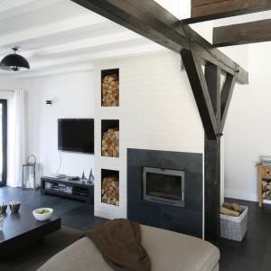 Urządzony w bieli salon ociepla drewno w dwóch rożnych wariantach - te będące częścią struktury budynku oraz te zgromadzone wokół kominka. Projekt: Kamila Paszkiewicz. Fot. Bartosz Jarosz.