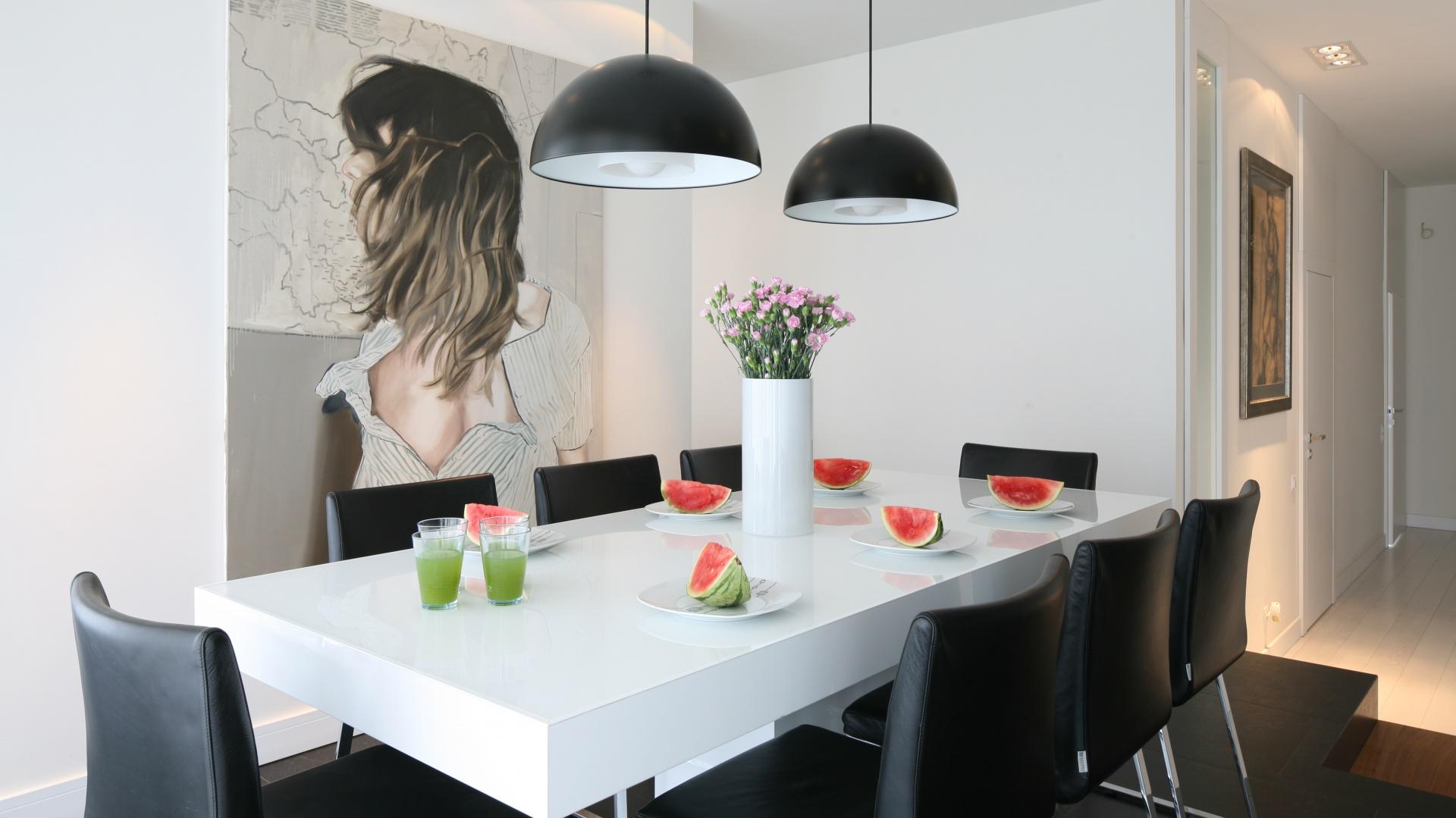 Dwie techniczne lampy wiszące nad stołem stanowią z nim harmonijną kolorystyczną całość. Biały blat i czarne krzesła korespondują z barwą plastikowych kloszy lamp - czarnych od zewnątrz i białych wewnątrz. Prostota i elegancja. Projekt: Dominik Respondek. Fot. Bartosz Jarosz.