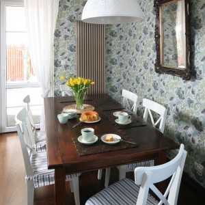 Ścianę w jadalni pokrywa tradycyjna, wzorzysta tapeta. Idealnie komponuje się ona z klasycznymi meblami i tekstylnymi siedzeniami krzeseł. Całe pomieszczenie ma niezwykle romantyczny, wdzięczny charakter. Projekt: Magdalena Misaczek. Fot. Bartosz Jarosz.