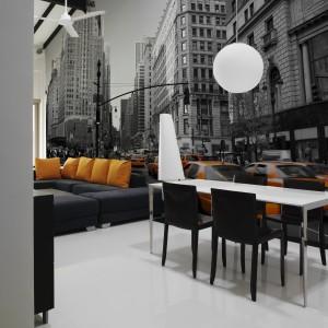 Stylowa fototapeta z czarno-białą fotografią ulic Nowego Jorku, z wyróżnionymi kolorem taksówkami. Poprowadzona po całej ścianie, łączącej salon z jadalnią. Kolorystyką komponuje się z umeblowaniem wnętrza. Fot. Artofwall, fototapeta City.