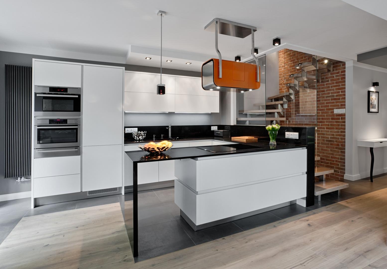 W tej pięknej kuchni, graniczącej z przeszkloną klatką schodową industrialny klimat buduje cegła na ścianie za przeszkleniem oraz nowoczesne meble z gładkimi, matowymi frontami i efektownym, połyskującym, przedłużonym blatem półwyspu. Dopełnieniem całości jest nowoczesny okap. Fot. Atlas Meble Kuchenne, model Oktawia listwowy.