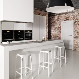 Białe meble kuchenne o nowoczesnej formie, w których tradycyjne fronty zastąpiono unikalnym frezowaniem. Gładkie powierzchnie i uniwersalna biel idealnie komponują się z cegłą na ścianie i loftowymi lampami. Fot. Zajc Kuchnie, kuchnia Z4/009.