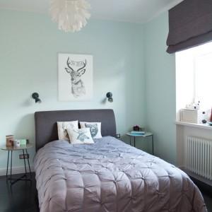 W sypialni przytulności wnętrzu dodają tekstylia. Dekoracyjne poduszki w skandynawskim stylu korespondują z obrazem na ścianie, przedstawiającym głowę jelenia. Funkcję tradycyjnych szafek nocnych pełnią niewielkie stoliki na delikatnych nogach, nadając wnętrzu lekkiego wyrazu. Całość utrzymano w różnych odcieniach szarości z subtelnym, chłodnym seledynowym akcentem na ścianach. Projekt: Magdalena Ilmer, Boho Studio. Fot. Boho Studio.