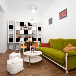 Meble w salonie to eklektyczny miks nowoczesnych kształtów ze stylizowanymi elementami. Tapicerowana kanapa stoi na białych, delikatnie zdobionych nogach, regał jest pochwałą nowoczesności i pasuje kolorem i stylem do białych, prostych pufów i stolika kawowego na metalowych kółkach. Stół jadalniany to z kolei wyjątkowy zabytek, pochodzący ze strychu właścicielki. Projekt: Magdalena Ilmer, Boho Studio. Fot. Boho Studio.