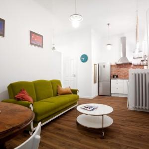 Kuchnia i salon tworzą wspólną otwartą przestrzeń, którą umownie rozgranicza jedynie niewielka ścianka, zamykająca kuchenny blat, na której zamontowano grzejnik. Projekt: Magdalena Ilmer, Boho Studio. Fot. Boho Studio.