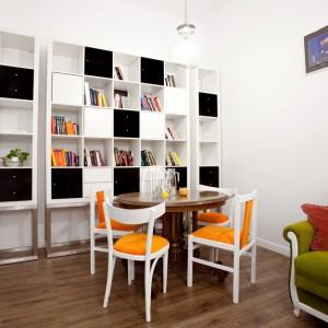 W salonie wzrok przyciąga oryginalny regał, w którym otwarte półki zestawiono z frontami w kolorach czerni i bieli. Mebel nadaje wnętrzu nowoczesny charakter, harmonizując z oświetleniem w delikatnie industrialnym stylu. Projekt: Magdalena Ilmer, Boho Studio. Fot. Boho Studio.