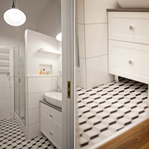 Niewielką łazienkę urządzono w optycznie powiększającą przestrzeń bieli, z dyskretnymi szarymi akcentami. Na podłodze posadzka wg. projektu Macieja Zienia. Projekt: Magdalena Ilmer, Boho Studio. Fot. Boho Studio.