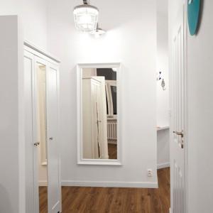 W korytarzu wisi efektowna, inudstrialna lampa. Niewielką przestrzeń optycznie powiększają lustra. Projekt: Magdalena Ilmer, Boho Studio. Fot. Boho Studio.